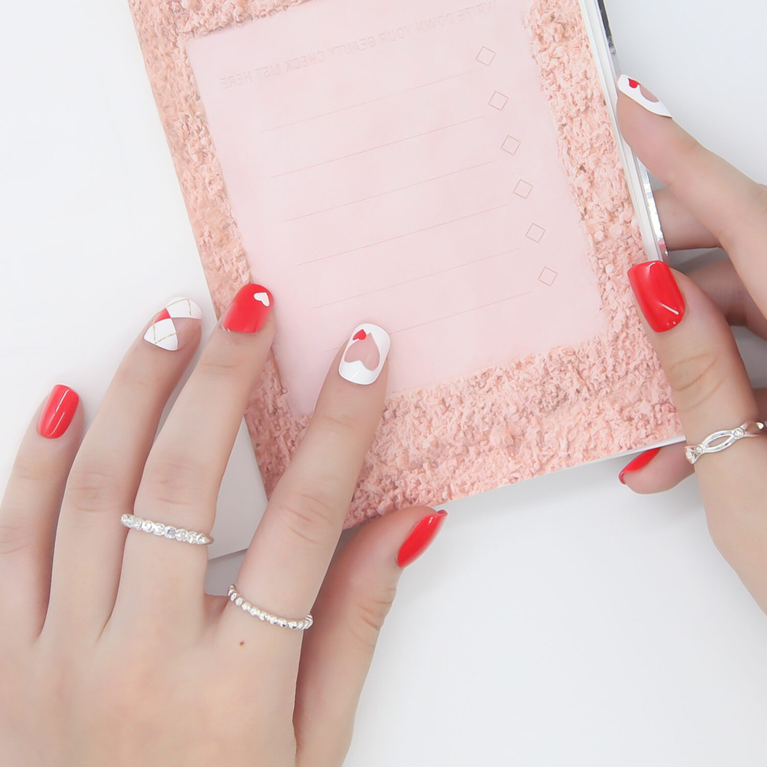XOXO red and white heart Stick On Nails on hand. Fake Nails, Press On Nails, Artificial Nails, Nail Tips, DIY Manicure, MUSE & Co.